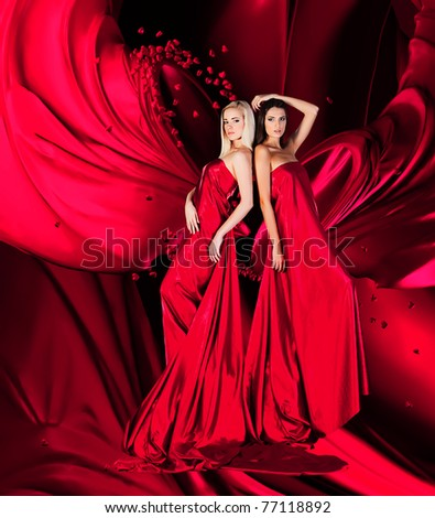 two women in blue dress with long hair and hearts  on red drapery - stock photo