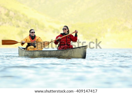 Two women in dry suits paddling a canoe across the lake. - stock photo