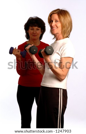 two women in exercise mode with intentional light and focus on instructor - stock photo