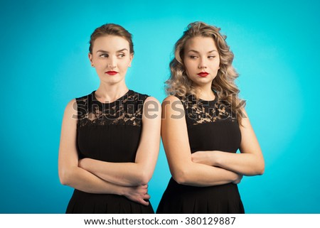 Two women in identical black dresses are angry at each other  - stock photo
