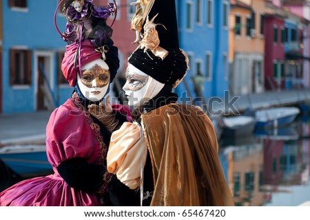 Two women in mask on Venetian carnival. Burano island, Venice, Italy. - stock photo