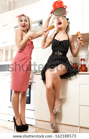 Two women in pin up style. Womens chefs cooking in the kitchen. - stock photo