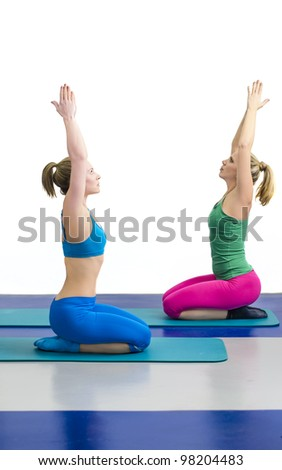 Two women in the gym doing yoga excercise with hands in the air concentrating and relaxing. One woman is in blue training outfit, another is in violet and green. - stock photo