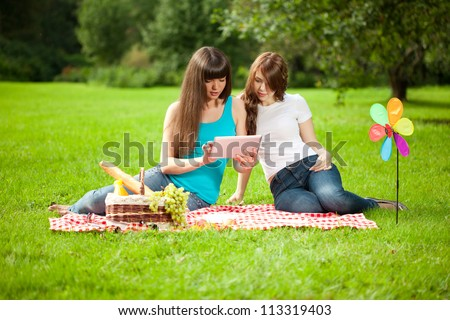 Two women in the park on a picnic and Tablet PC - stock photo