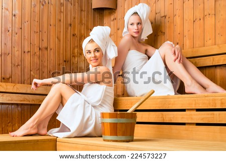 Two Women in wellness spa relaxing in wooden sauna - stock photo