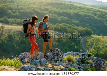Two women is trekking in the Crimea mountains with backpacks - stock photo