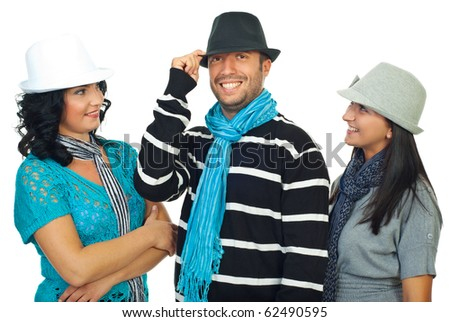 Two women looking with admiration  at a cool man in hat and all of them smiling and laughing isolated on white background - stock photo