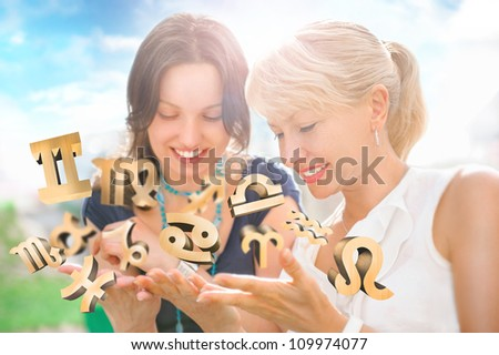 Two women mother and daughter sitting at summer park and having fun while discussing horoscope and different zodiac symbols appearing from their hands. Lots of copyspace - stock photo