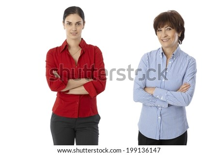 Two women, mother and daughter standing arms crossed, looking at camera, smiling over white background. - stock photo