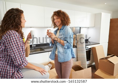 Two Women Moving Into New Home And Unpacking Boxes - stock photo