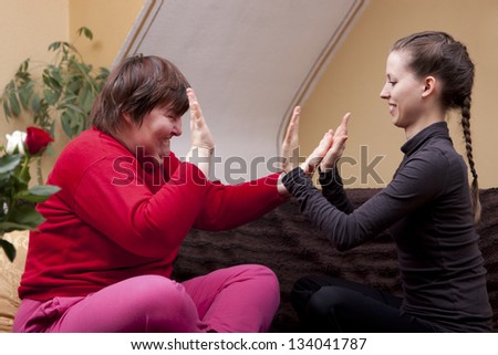 Two women, one of them disabled, making rhythm exercises - stock photo