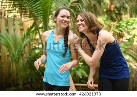 Two women or sisters sharing a funny moment in friendship - stock photo