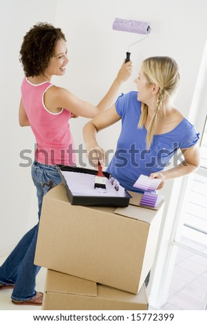 Two women painting room in new home smiling - stock photo