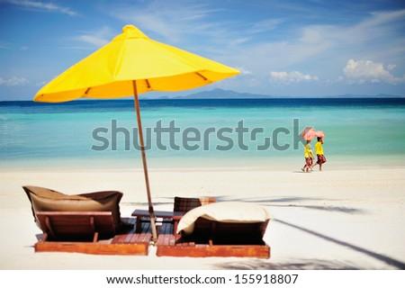 Two women pass by the yellow beach umbrella.  - stock photo