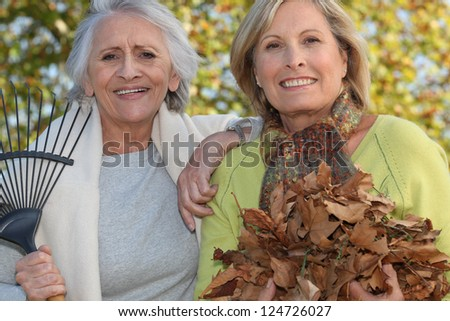 Two women raking leaves - stock photo