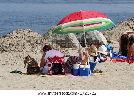 Two women relaxing on the beach under an umbrella - stock photo