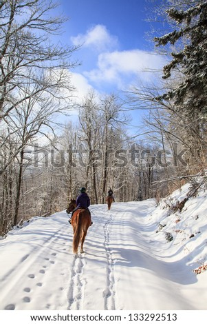 Two women ride along in the fresh snow on a bright winter morning. Snowshoe, WV - stock photo
