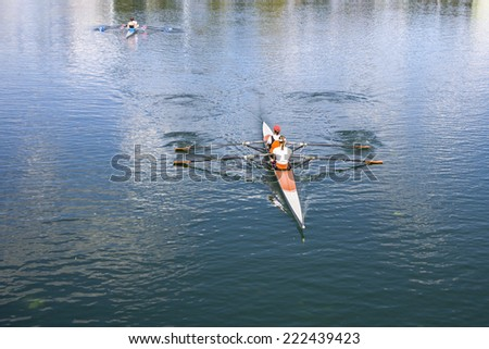 Two Women Rower in a boat, rowing on the tranquil lake - stock photo