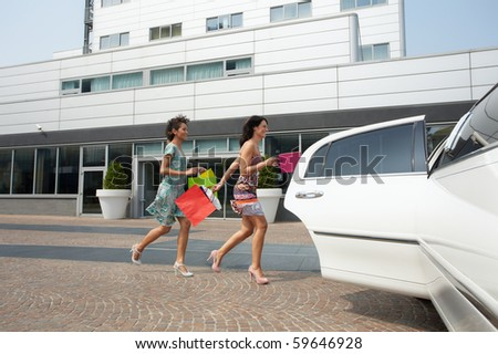 two women running into limousine with shopping bags. Horizontal shape, full length - stock photo