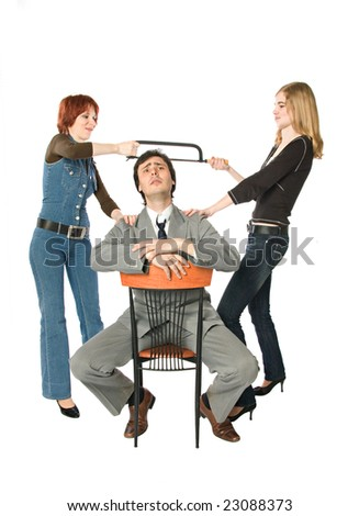 Two women sawing a man - stock photo