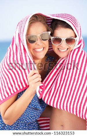 Two Women Sheltering From Sun On Beach Holiday - stock photo