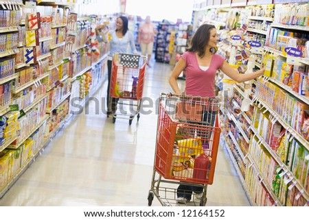 Two women shopping in supermarket grocery aisle - stock photo