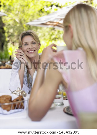 Two women sitting at outdoor dining table and talking - stock photo