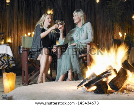 Two women sitting by bonfire at outdoor nightclub toasting - stock photo