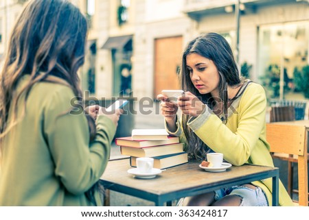 Two women sitting in a bar and staring at mobile phones - Girls watching a video online on portable device - stock photo