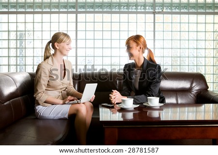 Two women sitting on couch and talking. One of them doing something on laptop. - stock photo