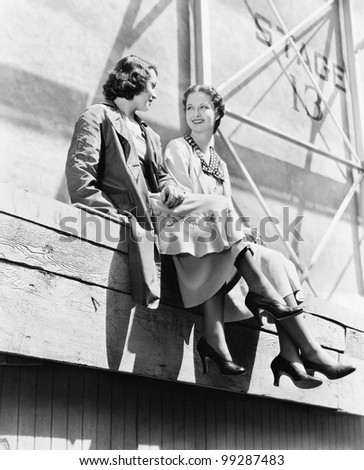 Two women sitting together on scaffolding - stock photo