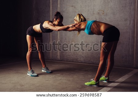 Two women stretching before gym workout - stock photo