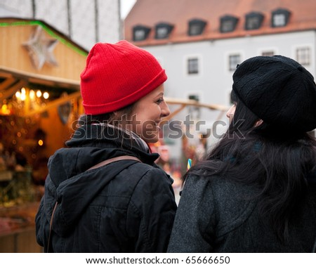 Two women strolling over Christmas market in front of a booth, it is cold - stock photo