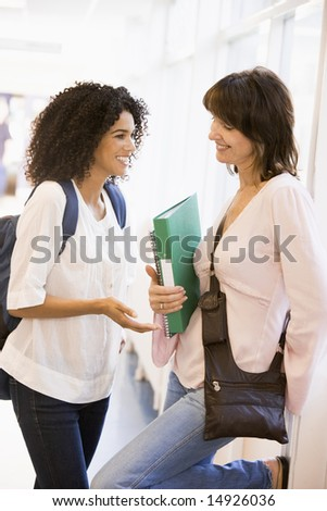 Two women students chatting in a campus corridor - stock photo