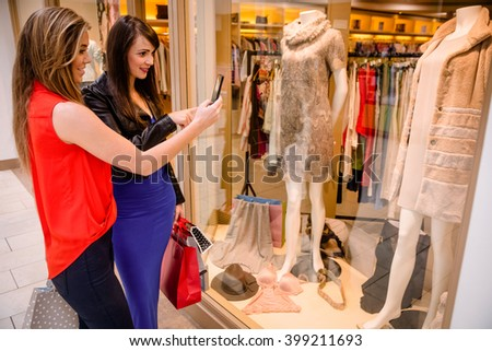 Two women taking a photo of a dress in window display in mall - stock photo