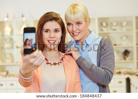 Two women taking a selfie while shopping in a jewelry store - stock photo