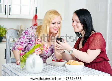 Two women talking using telephone - stock photo