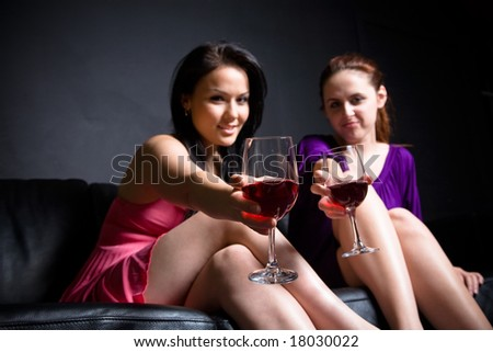 Two women toasting glasses of red wine (focus on the glass) at a party - stock photo