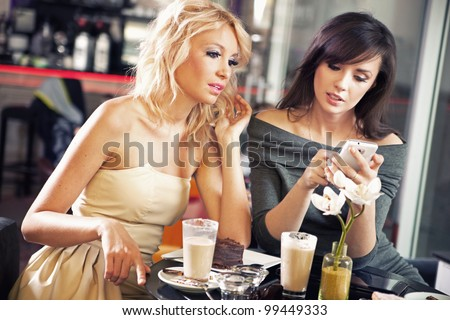 Two women using a smart phone - stock photo