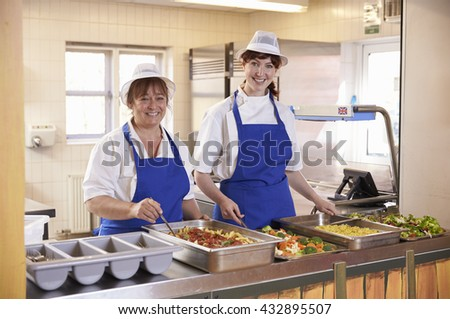 Two women waiting to serve lunch in a school cafeteria - stock photo