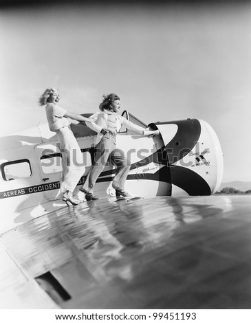 Two women walking on the wing of a plane - stock photo