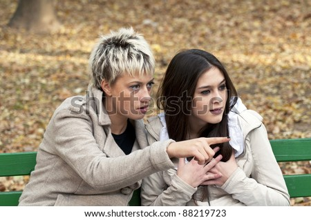 Two women whispering and smiling at the city park - stock photo