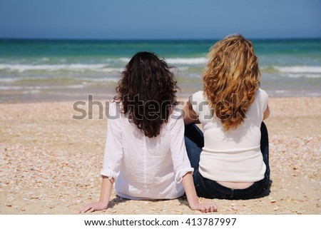 Two women with beautiful long hair are sitting on the beach - stock photo