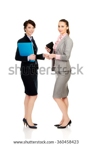 Two women with notebooks giving handshake. - stock photo