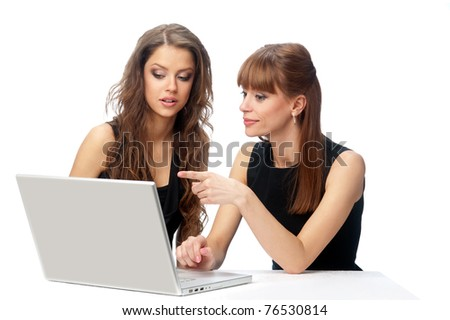 Two women working on a laptop computer. Isolated background - stock photo