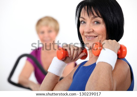 Two women working out in the gym - stock photo