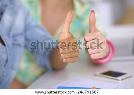 Two women working together at office, sitting and showing ok - stock photo