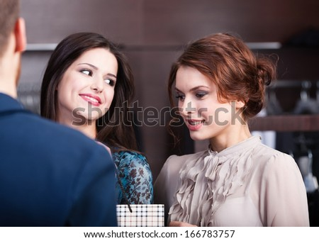 Two wonderful women talk to shop assistant - stock photo