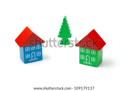 Two wooden block houses with a tree in the middle - stock photo