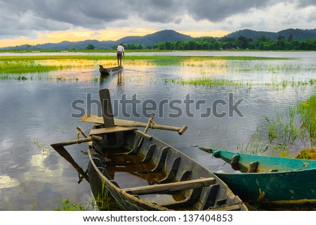 Two wooden boats are anchored, golden hours on the Lak lake, Dak Lak, Vietnam - stock photo